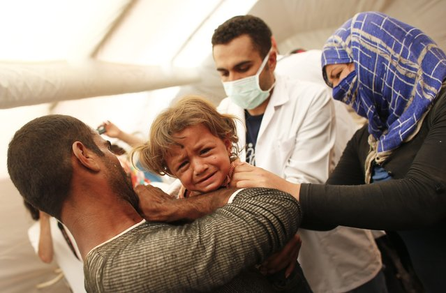 A medic examines a Kurdish Syrian refugee child inside a temporary medical facility for children on the Turkish-Syrian border near the southeastern town of Suruc in Sanliurfa province, in this September 24, 2014 file photo. (Photo by Murad Sezer/Reuters)