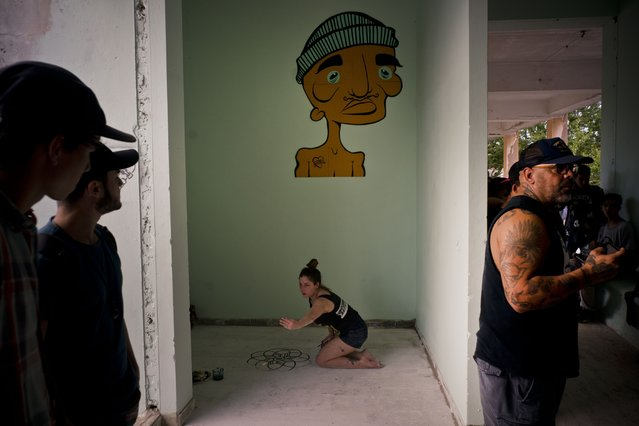 """In this January 11, 2018 photo, an artist decorates the floor with a mural during the inauguration of a new recreational space for skateboarders, created in an abandoned gym at the Educational complex Ciudad Libertad, a former military barracks that the late Fidel Castro turned into a school complex after the revolution in Havana, Cuba. The mural on the wall is by Kaya, the late son of Rene Lecour, who stands at right, who founded the skating association """"Amigo Skate Cuba"""" with his skate enthusiast son who wanted to find a way to support Cuba's emerging skater community. (Photo by Ramon Espinosa/AP Photo)"""
