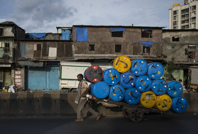 A porter transports a cart loaded with empty plastic drums to a recycling factory at a slum in Mumbai June 10, 2014. (Photo by Danish Siddiqui/Reuters)