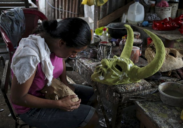 A woman paints a devil mask in preparation for the Los Aguizotes festival  in the indigenous community of Monimbo in Masaya, Nicaragua, October 16, 2015. (Photo by Oswaldo Rivas/Reuters)