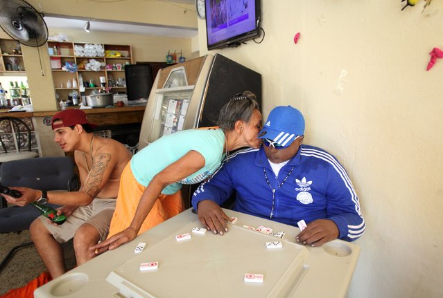 The mother of Jomar Aguayo plants a kiss on the cheek of her dead son while his body is seated at a table with domino tiles in San Juan, October 19, 2015. (Photo by Alvin Baez/Reuters)
