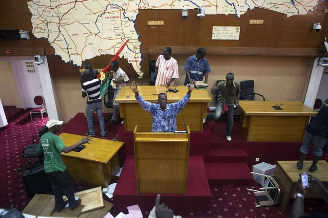 Anti-government protesters take over the parliament building in Ouagadougou, capital of Burkina Faso, in this October 30, 2014 file photo. I'd been following the protesters since the morning. Parliament was set to vote on a law extending the current president's 27-year term and the people were protesting against that. (Photo and caption by Joe Penney/Reuters)
