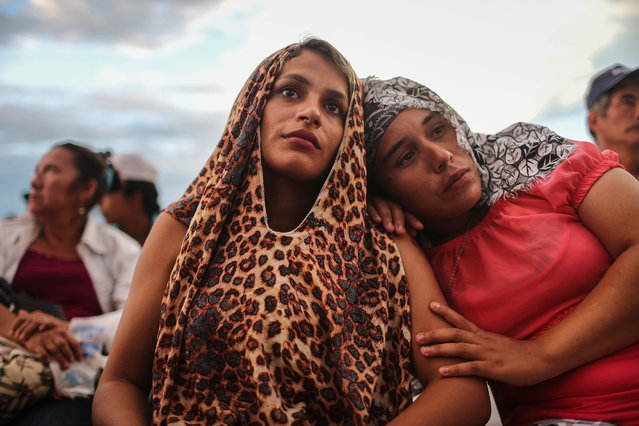 Revolutionary Armed Forces of Colombia (FARC) rebel (R) and supporters watch a live broadcast of the somber peace agreement signing ceremony while in the remote Yari plains where the peace accord was ratified by the FARC on September 26, 2016 in El Diamante, Colombia. The peace agreement attempts to end the 52-year-old guerrilla war between the FARC and the state, the longest-running armed conflict in the Americas which has left 220,000 dead. The final agreement will be put to vote by the public in a referendum on October 2. The plan calls for a disarmament and re-integration of most of the estimated 7,000 FARC fighters. (Photo by Mario Tama/Getty Images)