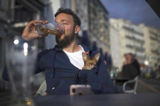 Naguey drinks a final beer with his cat Nela before bars and restaurants close, in Marseille, southern France, Sunday September 27, 2020. As restaurants and bars in Marseille prepared Sunday to shut down for a week as part of scattered new French virus restrictions, Health Minister Olivier Veran insisted that the country plans no fresh lockdowns. (Photo by Daniel Cole/AP Photo)