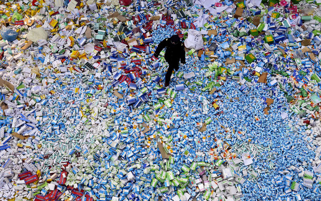 This picture taken on March 14 shows a Chinese policeman walking across a pile of fake medicines seized in Beijing in recent months, which were later destroyed. The rapid growth of Internet commerce has led to an explosion of counterfeit drugs sold around the world, with China the biggest source of fake medicines, pharmaceutical experts said as the illicit trade is now believed to be worth around 75 billion USD globally, with criminal gangs increasingly using the web to move their products across borders. (Photo by AFP Photo)