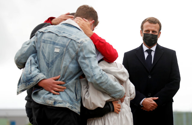 French President Emmanuel Macron (R) stands next to French aid worker Sophie Petronin (C) who is welcomed by her family after suspected jihadist hostage-takers freed the 75-year-old from nearly four years of captivity in Mali upon her arrival at the Villacoublay military airport near Paris on October 9, 2020. Petronin was released along with a top Malian politician and two Italian hostages late on October 8, 2020. The last French citizen known to have been held hostage anywhere in the world since her abduction in 2016, a white-robed Petronin was embraced by her son as she touched down in Mali's capital, Bamako. (Photo by Gonzalo Fuentes/Pool via AFP Photo)