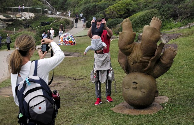 A father holds his son upside down to match a bronze sculpture by Thai artist Naidee Changmoh entitled 'Fun' during the 19th annual Sculptures by the Sea exhibition in Sydney, October 23, 2015. (Photo by Jason Reed/Reuters)