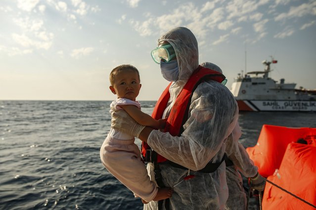 """A Turkish coast guard officer, wearing protective gear to help prevent the spread of coronavirus, carries a child off a life raft during a rescue operation in the Aegean Sea, between Turkey and Greece, Saturday, September 12, 2020. Turkey is accusing Greece of large-scale pushbacks at sea – summary deportations without access to asylum procedures, in violation of international law. The Turkish coast guard says it rescued over 300 migrants """"pushed back by Greek elements to Turkish waters"""" this month alone. Greece denies the allegations and accuses Ankara of weaponizing migrants. (Photo by Emrah Gurel/AP Photo)"""