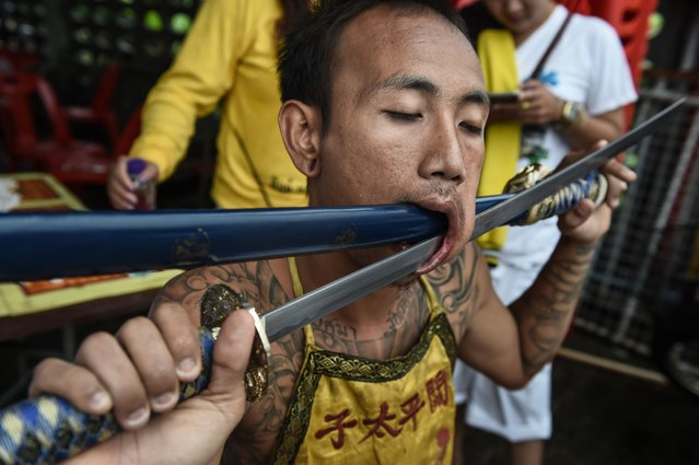A devotee of the Nine Emperor Gods is seen with swords through his face during the annual Phuket Vegetarian Festival in the southern province of Phuket on October 3, 2016. (Photo by Lillian Suwanrumpha/AFP Photo)