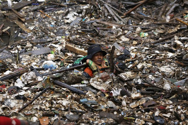 A volunteer clears rubbish from the Ciliwung River in the Jatinegara district of Jakarta, December 3, 2014. More than 1,000 soldiers and volunteers cleared 80 tons of rubbish after flooding hit parts of the capital last week, local media reported. (Photo by Reuters/Beawiharta)