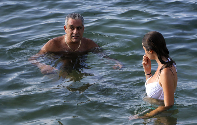 "In this October 10, 2015 photo, businessman Ziad Chamoun, a Boston-area restaurant and club owner turned wine importer, swims with guide Hannah Berkeley as he spends the afternoon at a waterfront villa in Havana, Cuba, Saturday. ""The next big bubble is going to be nightlife. That's what happened to Cancun,"" said Chamoun. (Photo by Desmond Boylan/AP Photo)"