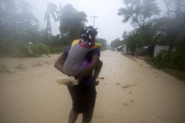A woman and a child walk in a waterlogged street as they head to a shelter under the pouring rain caused by Hurricane Matthew, in Leogane, Haiti. Tuesday, October 4, 2016. (Photo by Dieu Nalio Chery/AP Photo)