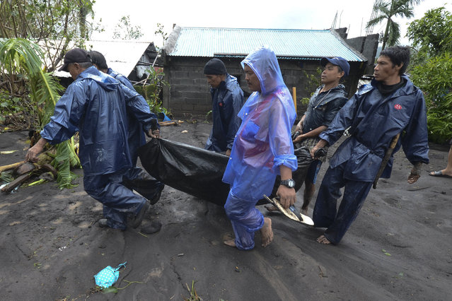 Rescuers carry the body of a man that drowned in floods as Typhoon Goni hit Guinobatan, Albay province, central Philippines, Sunday, November 1, 2020. (Photo by AP Photo/Stringer)