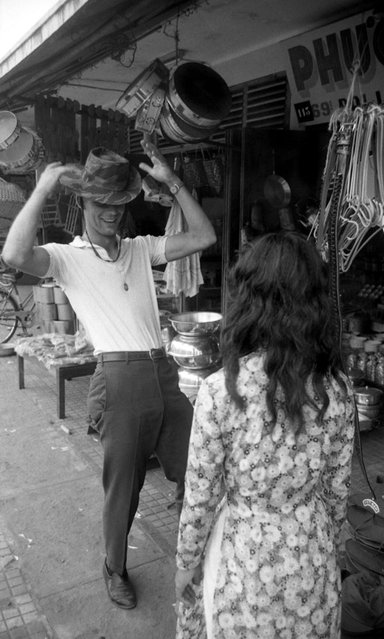 James Farley takes a fancy to a bush hat and models it in the street, Da Nang, March 1961. (Photo by Larry Burrows/Time & Life Pictures)