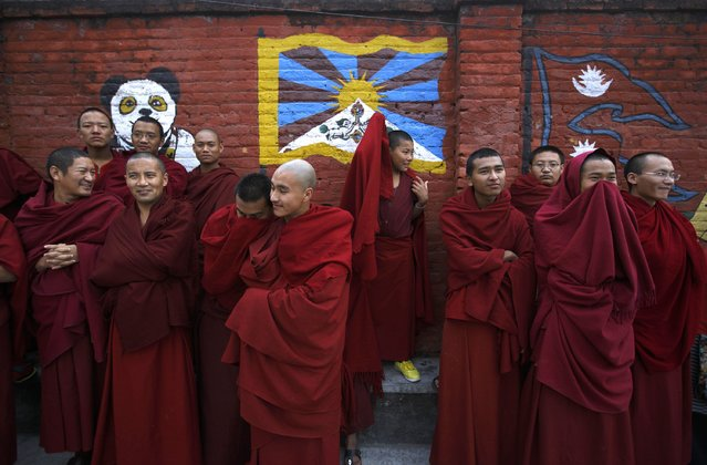 Tibetan monks stand in front of a wall mural depicting the Tibetan flag during an event organised by the Tibetan Refugee Community in Nepal commemorating the 25th Anniversary of the Nobel Peace Prize conferment to their exiled Tibetan spiritual leader Dalai Lama and the 66th International Human Rights Day in Kathmandu December 10, 2014. (Photo by Navesh Chitrakar/Reuters)