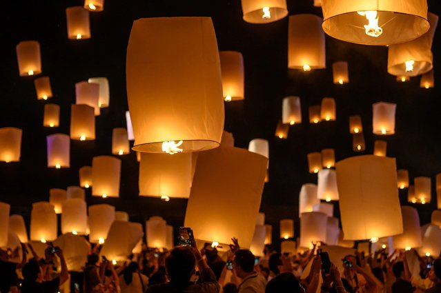 People light and release paper lanterns during the celebration of Loy Krathong festival outside Chiang Mai on October 31, 2020 (Photo by Mladen Antonov/AFP Photo)
