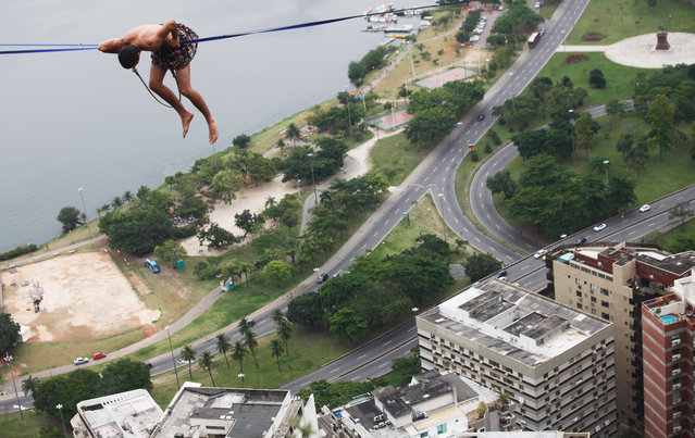 A participant balances on a slackline set up between rocks in the Cantagalo favela community during the Highgirls Brasil festival on November 2, 2015 in Rio de Janeiro, Brazil. (Photo by Mario Tama/Getty Images)