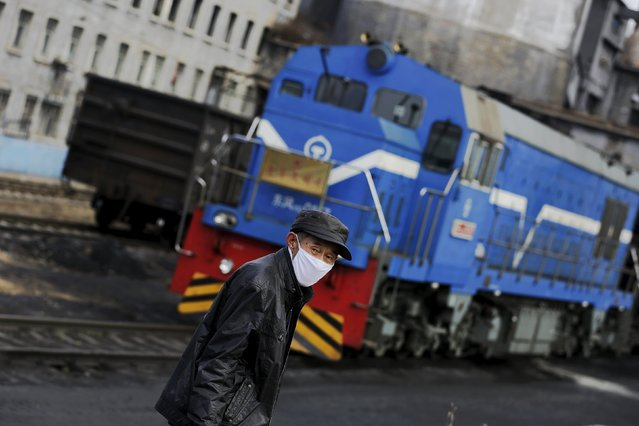 A local villager wearing a mask walks past a coal train outside a coal mine from the state-owned Longmay Group on the outskirts of Jixi, in Heilongjiang province, China, October 22, 2015. (Photo by Jason Lee/Reuters)