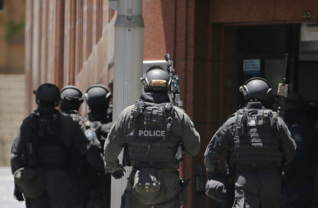 Armed police stand at the ready close to a cafe under siege at Martin Place in Sydney, Australia, Monday, December 15, 2014. A gunman took an unknown number of people hostage inside a downtown Sydney chocolate shop and cafe at the height of Monday morning rush hour, with two people inside the cafe seen holding up a flag believed to contain an Islamic declaration of faith. (Photo by Rob Griffith/AP Photo)