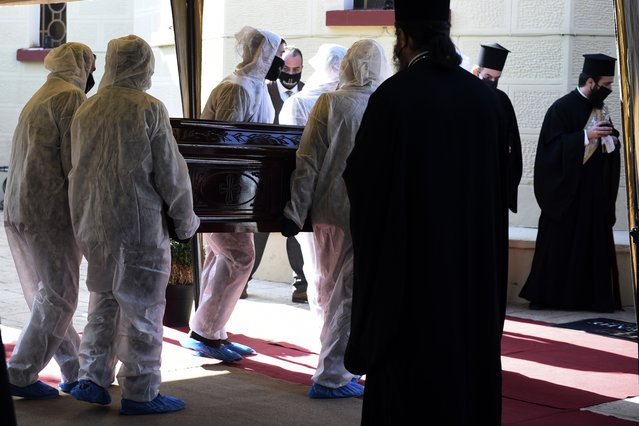 Priests wearing face masks to protect against the spread of the coronavirus, attend the funeral of senior clergyman Ioannis of Lagadas after he died of COVID-19,  in Greece's Orthodox Church, in the northern city of Thessaloniki, Greece, Monday, November 16, 2020. Metropolitan Bishop Ioannis of Lagadas, 62, was an outspoken advocate of maintaining communion ceremonies – at which worshipers are given bread as well as wine with a shared spoon – during the pandemic, arguing that there was no risk of transmission. (Photo by Giannis Papanikos/AP Photo)