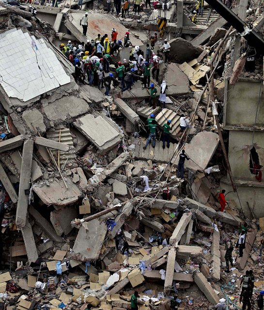 Rescuers work at the site of the building collapse. (Photo by A. M. Ahad/Associated Press)