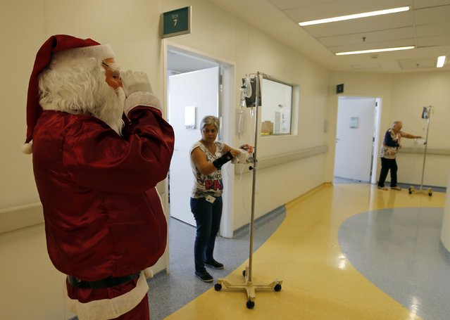 A man dressed as Santa Claus visits cancer patients who are undergoing chemotherapy at the Cancer Institute in Sao Paulo December 19, 2014. (Photo by Paulo Whitaker/Reuters)