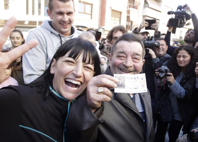 """Juan Lopez holds his lottery ticket with the winning number of Spain's Christmas Lottery """"El Gordo"""", together with his daughter Pilar in La Eliana near Valencia December 22, 2014. (Photo by Heino Kalis/Reuters)"""
