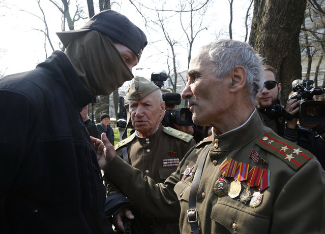 Soviet army veterans talk with an ultra-right activist, at the Soviet-era monument to General NIkolai Vatutin in Kiev, Ukraine, Friday, April 13, 2018. Activists of the Right Sector group on Friday splashed red paint on the Soviet-era monument to Nikolai Vatutin, a Red Army general who died in fighting during WW II. They also engaged in scuffles with supporters of an opposition party who attempted to put flowers to the monument in the Ukrainian capital, Kiev. (Photo by Efrem Lukatsky/AP Photo)