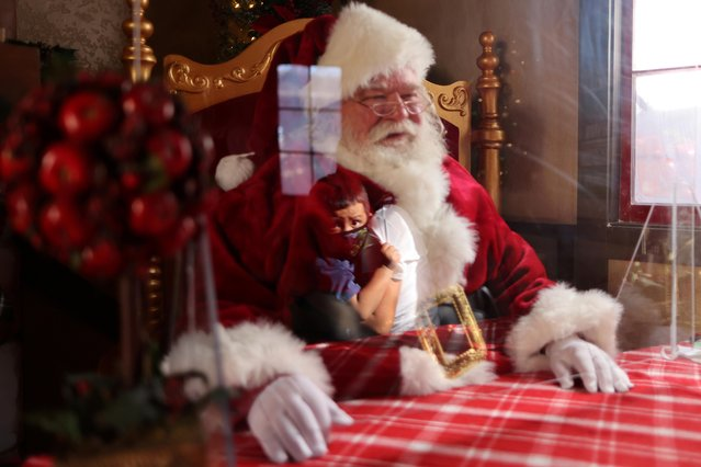 Panchito Vicente, 2, is reflected in plexiglass as he visits Santa Claus, Ray Hamlett, 74, at the Citadel Outlet mall, as the global outbreak of the coronavirus disease (COVID-19) continues, in Commerce, California, U.S., December 3, 2020. (Photo by Lucy Nicholson/Reuters)