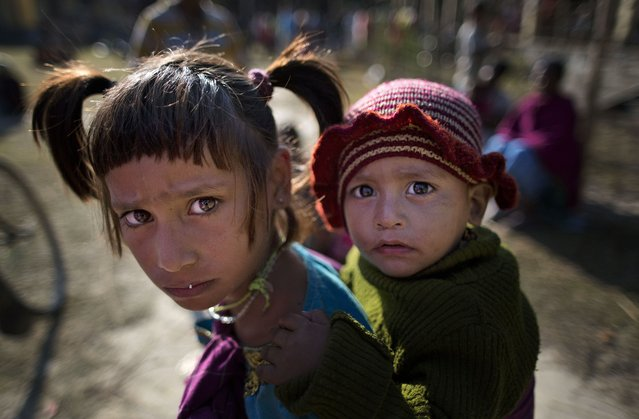 Indian tribal children react to camera at a relief camp at Tinsuti village in Sonitpur district of Indian eastern state of Assam, India, Thursday, December 25, 2014. Police says the death toll from rebel violence in remote northeastern India has risen to over 70 with the recovery of more bodies from abandoned villages. (Photo by Anupam Nath/AP Photo)