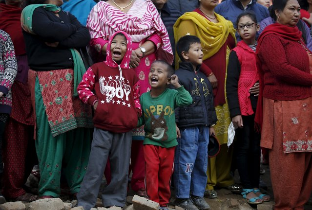 """Children observe the Newari New Year parade that falls during the Tihar festival, also called Diwali, in Kathmandu, Nepal November 12, 2015. The Newar community observes the start of their Newari New Year 1136, in accordance with their lunar calendar, by worshipping their spiritual selves in a ritual known as """"mahapuja"""". (Photo by Navesh Chitrakar/Reuters)"""