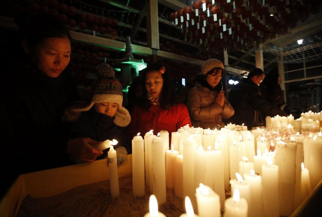 A boy lights a candle with his mother before a ceremony to celebrate the new year at Bongeun Buddhist temple in Seoul December 31, 2014. (Photo by Kim Hong-Ji/Reuters)
