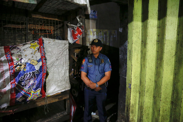 A policeman secures the entrance to the alley where a man was killed during a police drugs buy-bust operation in Manila, Philippines late October 21, 2016. (Photo by Damir Sagolj/Reuters)