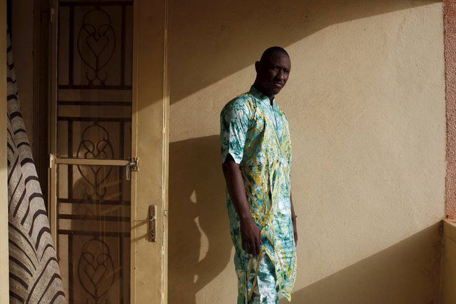 Bazin designer Baba Sereme poses for a picture in a bazin outfit he dyed at his home in Bamako, Mali, October 8, 2015. (Photo by Joe Penney/Reuters)