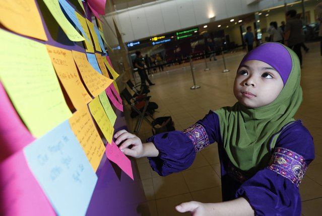 Singaporean six-year old Aris Marissa places a post-it note on a board of well wishes for the passengers of the missing AirAsia flight QZ 8501 outside the relative's holding area at Changi airport in Singapore, 30 December 2014. The search for a missing AirAsia plane that left Indonesia with 162 people on board expanded on 30 December, with more aircraft and ships set to scour a wider area. (Photo by Rancis R. Malasig/EPA)