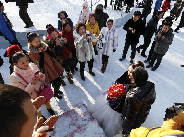 Attendants take pictures of a newly-wed couple after their group wedding ceremony which was held as a part of the Harbin International Ice and Snow Festival in the northern city of Harbin, Heilongjiang province January 6, 2015. (Photo by Kim Kyung-Hoon/Reuters)