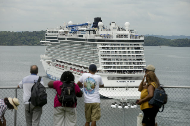Tourists watch the Norwegian Bliss ship transit through the Panama Canal, seen from the Visitors Center at the Panama Canal in Agua Clara, Panama, Monday, May 14, 2018. Norwegian Bliss, one of the largest ships to ever navigate the Panama Canal, is the largest ship in Norwegian's fleet, with 20 decks and a capacity of about 4,000 passengers. (Photo by Arnulfo Franco/AP Photo)