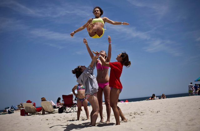 Emilie Sullivan is thrown into the air by her friends as they play on the first weekend of Jersey Shore beaches re-opening to the public, in Seaside Heights, New Jersey, on May 27, 2013. The region continues to recover and rebuild after Hurricane Sandy devastated parts of the coastline. (Photo by Kena Betancur/Getty Images)