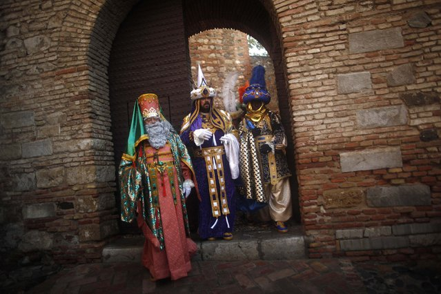 Men dressed as (L -R) Melchior, Gaspar and Balthasar, the Three Wise Men, leave the Alcazaba monument at the start of the traditional Epiphany parade in Malaga, southern Spain January 5, 2015. (Photo by Jon Nazca/Reuters)