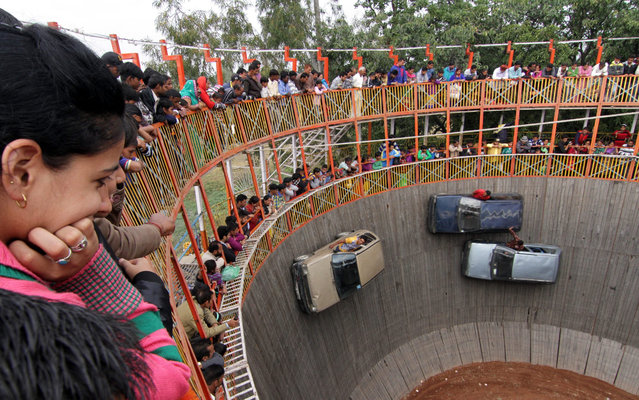 Indian stuntmen perform in the cars as villagers watch the show of 'Maut ka Kuan or Well of Death' during the annual Farmers Fair at Shama Chak Jhiri, some 22 km from Jammu the winter capital of Kashmir, India, 25 November 2015. Farmers in huge numbers from all over India gather to pay tribute to the Samadhi or tomb of legendary farmer Baba Jit Mal popularly known as Baba Jitto who sacrificed his life for the liberation of the farming community. (Photo by Jaipal Singh/EPA)