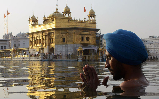 "An Indian Sikh devotee takes a dip in the holy sarover (water tank) at the Golden Temple on the eve of ""Ghallughara Diwas"", the 29th Anniversary of Operation Bluestar, in Amritsar on June 5, 2013. The 1984 assault on the Golden Temple complex by the Indian army was conducted in an attempt to arrest separatists Sikh leader Sant Jarnail Singh Bhindranwale and his militant followers who had initiated a movement for a separate Sikh state. (Photo by Narinder Nanu/AFP Photo)"