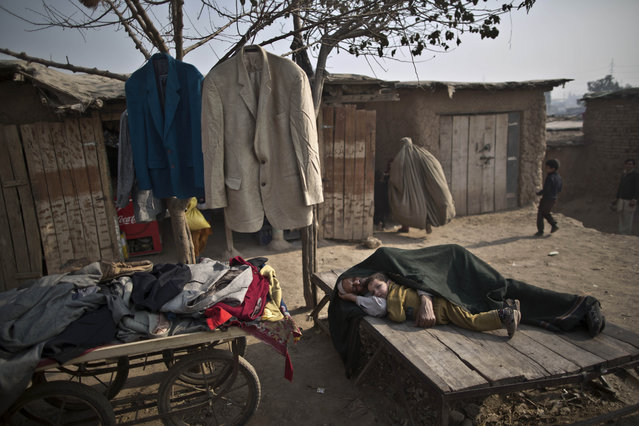 A Pakistani child who was displaced with his family from tribal areas lies next to his grandfather sleeping on a piece of wood next to his second hand clothes displayed for sale on a roadside in the outskirts of Islamabad, Pakistan, Friday, January 2, 2015. (Photo by Muhammed Muheisen/AP Photo)