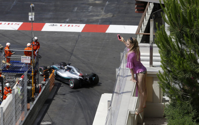 A woman takes pictures as Britain driver Lewis Hamilton steers his Mercedes during the third free practice at the Monaco racetrack, in Monaco, Saturday, May 26, 2018. The Formula one race will be held on Sunday. (Photo by Luca Bruno/AP Photo)