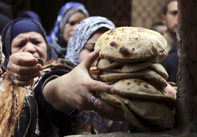 "A woman buys bread at a bakery in Cairo, January 8, 2015. The successful roll-out so far of a new ""smart card"" system to distribute subsidised bread has been a major achievement for Egypt's government, saving money while earning praise from families who no longer have to wake early to fight for loaves. (Photo by Mohamed Abd El Ghany/Reuters)"