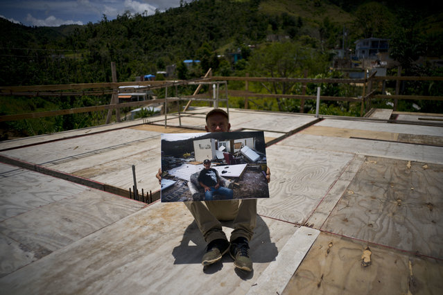 Luis Cosme poses on the roof of his new home as he holds a printed photo taken on October 1, 2017 showing him on his property destroyed by Hurricane Maria in the San Lorenzo neighborhood of Morovis, Puerto Rico, May 26, 2018. Cosme, who is retired from a cleaning company, rebuilt is home with cinderblocks instead of wood. (Photo by Ramon Espinosa/AP Photo)