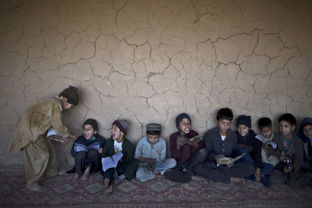 Afghan refugees and internally displaced Pakistani children attend their daily Madrassa, or Islamic school, at a mosque on the outskirts of Islamabad, Pakistan, Wednesday, January 14, 2015. (Photo by Muhammed Muheisen/AP Photo)