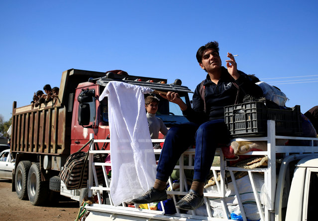 A man who just fled Kokjali near Mosul smokes a cigarette as he sits on a pickup truck on his way to a camp for the displaced, east of Mosul, Iraq November 3, 2016. (Photo by Zohra Bensemra/Reuters)