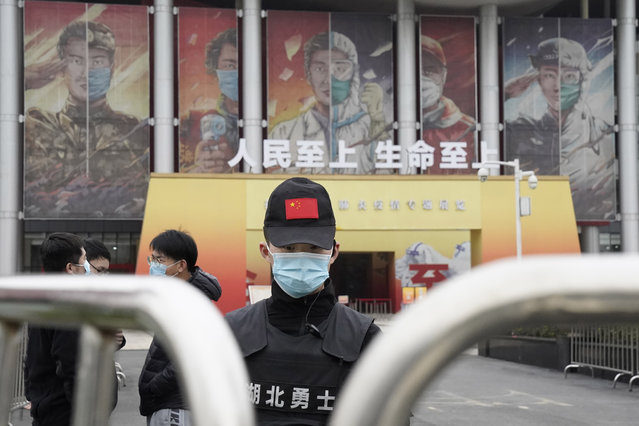 A security officer wearing a mask and a cap with the Chinese national flag guards the entrance after the World Health Organization team arrive at an exhibition about the fight against the coronavirus in Wuhan in central China's Hubei province on Saturday, January 30, 2021. The World Health Organization team investigating the origins of the coronavirus pandemic visited another Wuhan hospital that had treated early COVID-19 patients on their second full day of work on Saturday. (Photo by Ng Han Guan/AP Photo)