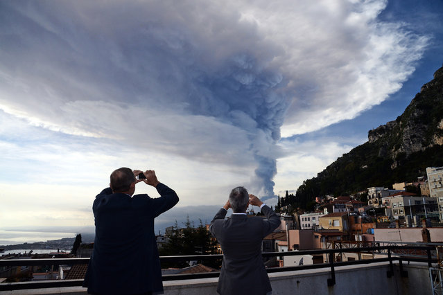 People take pictures of the smoke rising over the city of Taormina during an eruption of the Mount Etna, one of the most active volcanoes in the world, near Catania, on December 4, 2015. (Photo by Giovanni Isolino/AFP Photo)