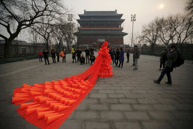 Chinese artist Kong Ning walks in her costume made of hundreds of orange plastic blowing horns during her art performance raising awareness of the hazardous smog in front of the Drum tower in a historical part of Beijing on a very polluted day December 7, 2015. (Photo by Damir Sagolj/Reuters)